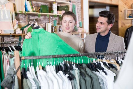 Smiling woman and man are choosing clothes and looking on green jacket in the store.