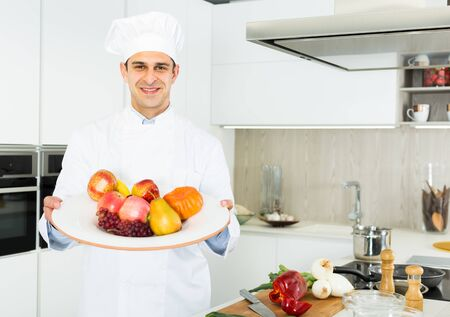 Professional male chef holding big plato with fruits in white uniform  on kitchen Foto de archivo
