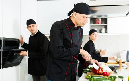 Positive female and male young cooks wearing black uniform working on kitchen