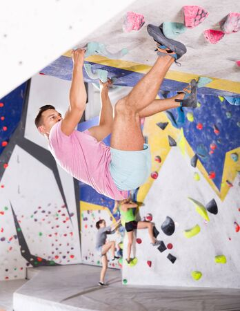 Confident male mountaineer climbing a artificial rock wall without a belay indoors