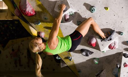 Confident female alpinist practicing rock-climbing without safety belts in dark bouldering gym