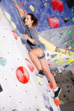 Glad  smiling sporty woman training at bouldering gym without special climbing equipment