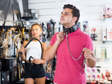 Adult couple choosing  leather lash and collar in the sex shop Stockfoto