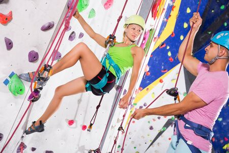 portrait of positive young couple of alpinist practicing in pair indoor rock-climbing on climbing wall in special equipment