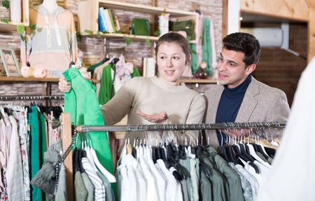 Couple is choosing jacket for her in the clothes store. Stockfoto
