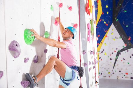 Sporty man dressed in rock climbing outfit training at bouldering gym