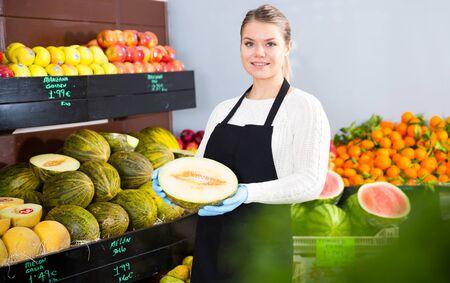 Smiling attractive salesgirl proposing half of ripe melon in greengrocery Zdjęcie Seryjne - 129258011