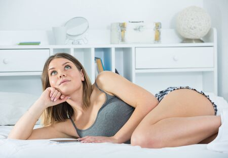 Portrait  of young sexy woman lying  with  smartphone in bed at home