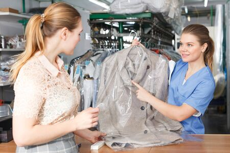 Young woman working with client in modern laundry, returning clothing after dry cleaning Stok Fotoğraf