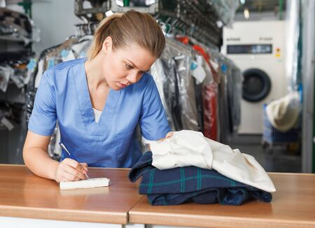 Competent female worker receiving clothing for dry cleaning writing receipt Zdjęcie Seryjne