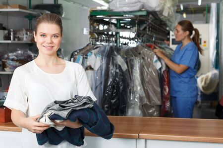 Portrait of happy young woman visiting modern dry cleaning