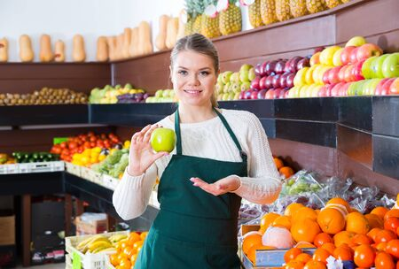 Nice female in apron fresh apples and fruits on the market Banque d'images