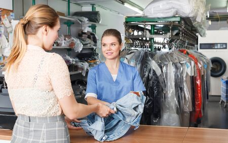 Glad woman working with client in modern laundry, receiving clothing for dry cleaning Фото со стока