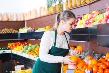 Modern female in apron selling fresh oranges and fruits on the market
