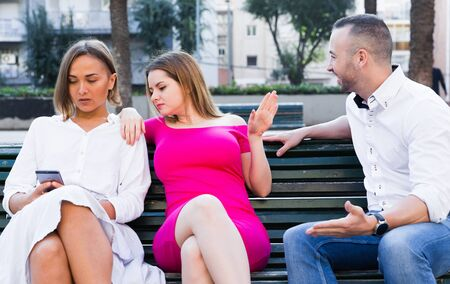 Young women are inaccessibility when man is playful talking with them in the park.