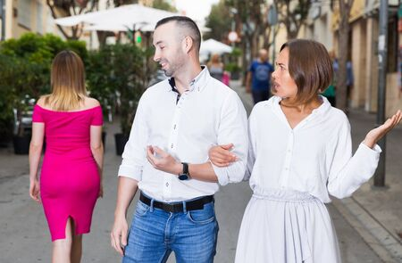 Young woman is resentmenting because her boyfriend was stared on other girl outdoors. Stockfoto
