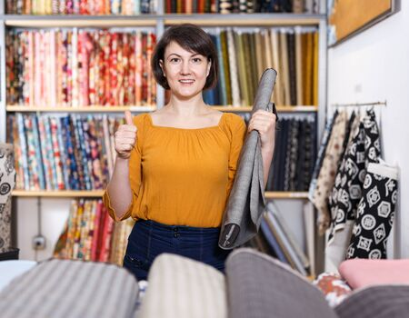 Portrait of happy attractive woman giving thumbs up in fabric shop