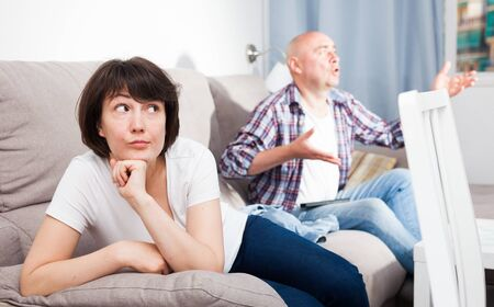 Sad woman sitting on the sofa. Next to her husband watching TV