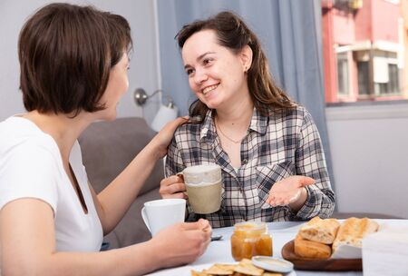 Two smiling women drinking tea with cookies in the kitchen