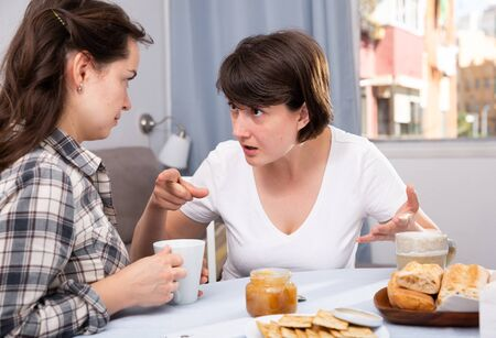 Emotional women having conflict at table with coffee  in home interior Stockfoto