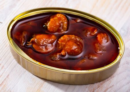 Open can of scallop Chlamys varia in sauce on wooden background. Seafood delicacy