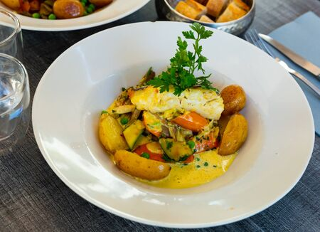 Spanish style hake steak served with baked vegetable and creamy sauce. Traditional French cuisine