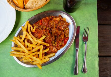 Top view of traditional Asturian beef stewed in vegetable sauce with green peas served with fried potatoes on metal plate Stockfoto