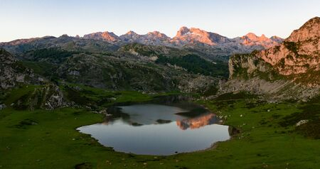 Serene landscape with one of Lakes of Covadonga and mountain range at dusk