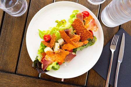 Top view of tasty Basque salad with sheep cheese, cured ham, romaine salad and tomatoes served on white plate. French cuisine