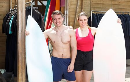 Nice people standing with surfboards in beach surf club