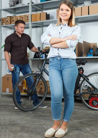 Positive woman is standing satisfied in the bike store