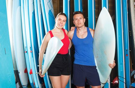 active sporty couple with surf equipment in surf club