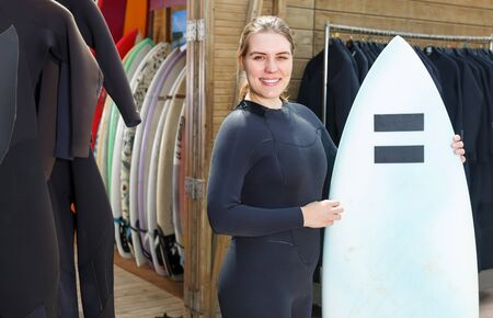 Pretty woman surf club instructor in wetsuit, standing outdoor with surfboard