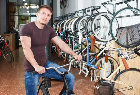 Portrait man who is satisfied of shopping and standing with bicylce in bike store.