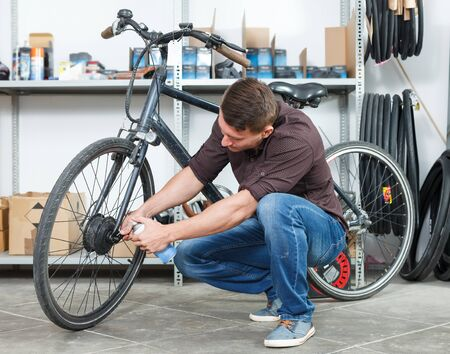 Portrait of young male master who is repairing bicycle in the workshop