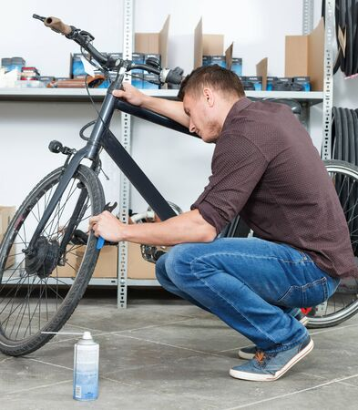 Portrait of male who is repairing bicycle in the workshop.