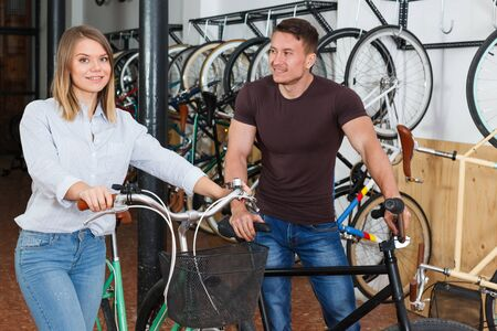 Man with woman are standing satisfied in the bike store.