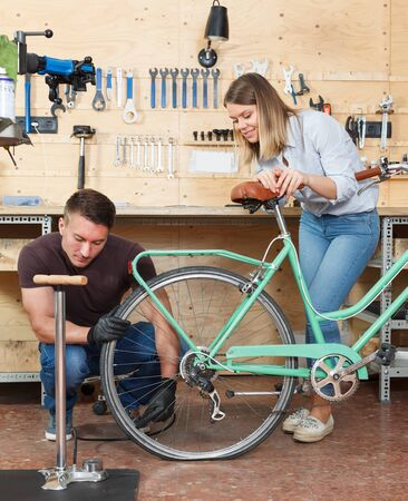 Mechanic helps a girl to repair a bicycle tire in the workshop. Stok Fotoğraf