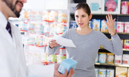Portrait of outraged female customer with medicines in drugstore