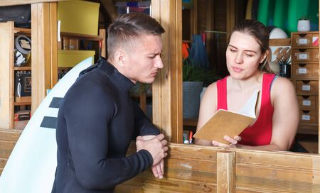 Happy athletic man talking to girl at reception while taking for rent surf equipment in surf club