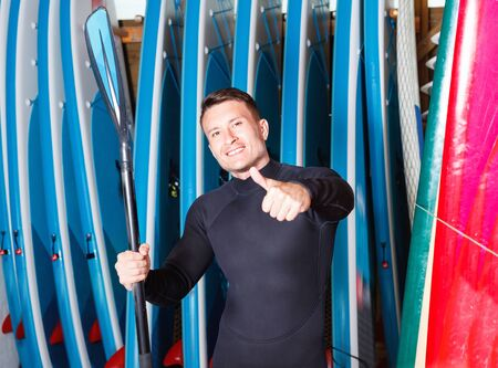 Portrait of sports  smiling glad friendly  man in wetsuit holding paddle in surf club Imagens