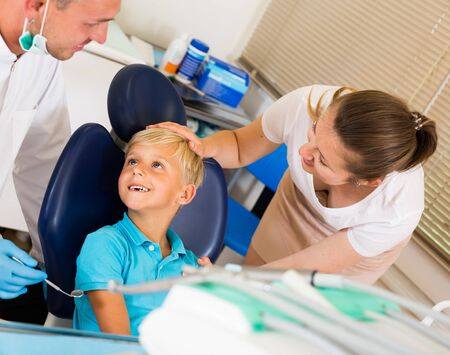 Boy with female are visiting dentist in dental office. Stock Photo