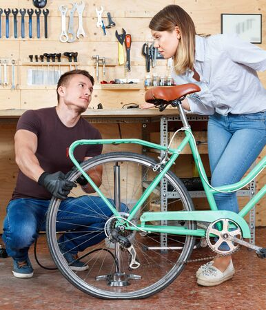 Glad man with woman are pumping the bicycle wheels in the workshop.