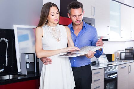 middle class positive family selecting modern kitchen furniture Stok Fotoğraf