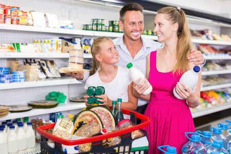 Smiling young family with girl shopping milk in food shop