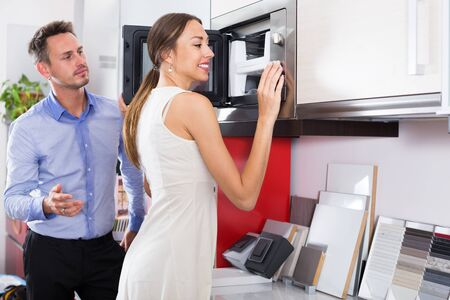 Young family couple looking for new modern mini oven in furniture showroom Stok Fotoğraf