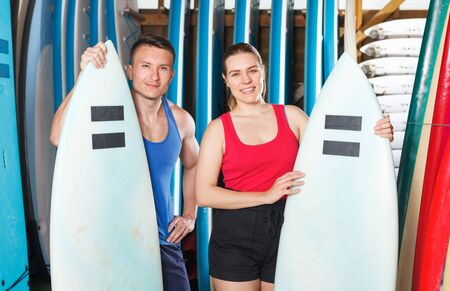 Adult people standing with surfboards in beach surf club