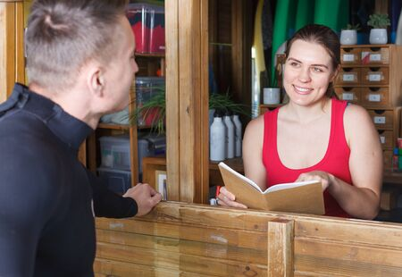 Adult athletic man talking to girl at reception while taking for rent surf equipment in surf club Banco de Imagens