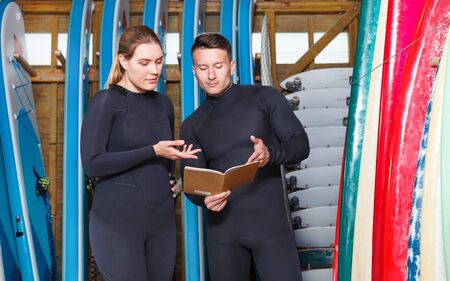 Young woman talking to athletic man while taking for rent a surf equipment in the surf club. Focus on both persons