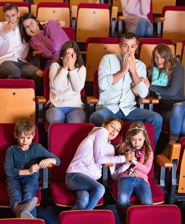 Group of cheerful people watching scary movie in cinema house